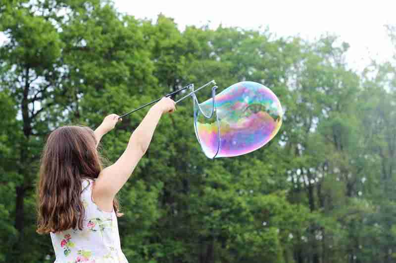 ילדה מפריכה בועות סבון בסדנת בועות סבון